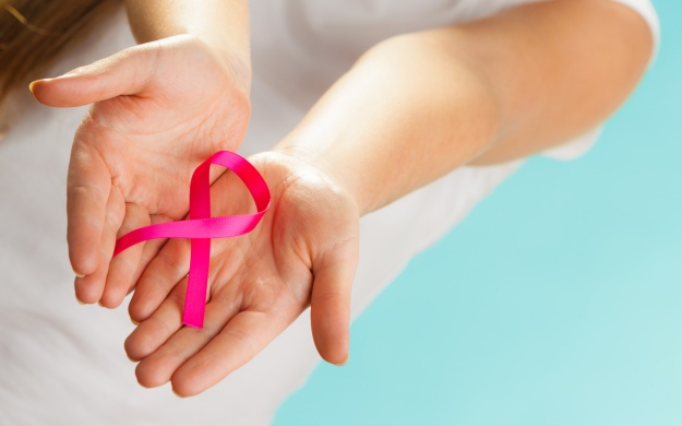 pink breast cancer awareness ribbon on womans hands